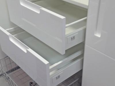 Выдвижные ящики глянцевых фасадов придают шкафу богатую роскошь