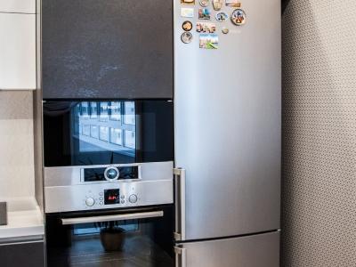 отдельно стоящий холодильник гармонично вписан в пенальную конструкцию