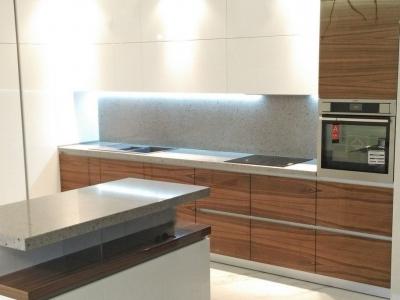 Каменная столешница со стеновой панелью гармонично сочетается с фактурами фасадов кухни