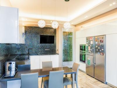 довольна большая кухня смотрится легко благодаря белому глянцу и удачно подобранному освещению