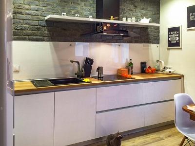Темная плитка с имитацией под кирпич служит отличным фоном для белой кухни.