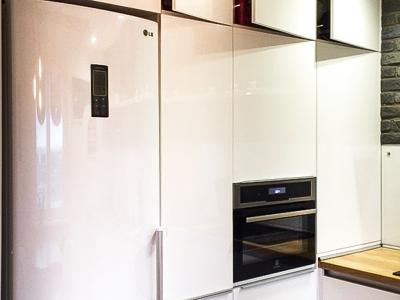 белая глянцевая эмаль  здорово маскирует холодильник в ряду мебельных шкафов.