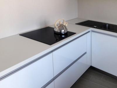 Мойка, варочная панель черного цвета хорошо сочетается с белым стеклом на фасадах кухни