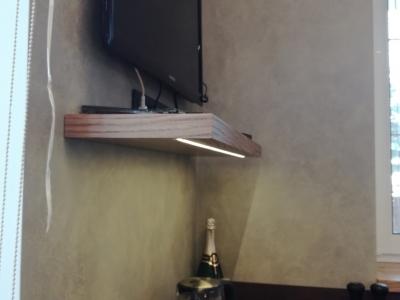 На полке из мдф шпонированного дубом с врезной подсветкой удобно расположился телевизор