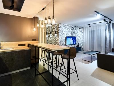 Большая барная стойка на опоре из сварной металлической конструкции, крашенной в чёрный цвет, служит также в качестве основной обеденной зоны