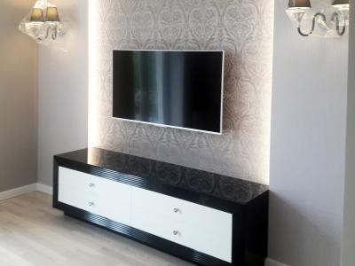 Встроенная подсветка в стену  подсвечивает глянцевые фактуры тумбы, облегчая общую конструкцию