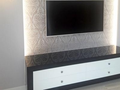 В одном пространстве с кухней на противоположной стене хорошо сочетается стеночка под телевизор