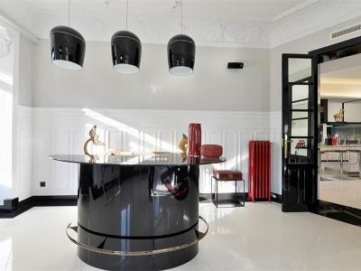 Отдельно стоящая барная стойка в соседней комнате имеет закаленную стеклянную столешницу
