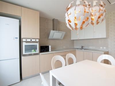 Шпонированные кухонные фасады бука придают интерьеру розово-бежевые оттенки