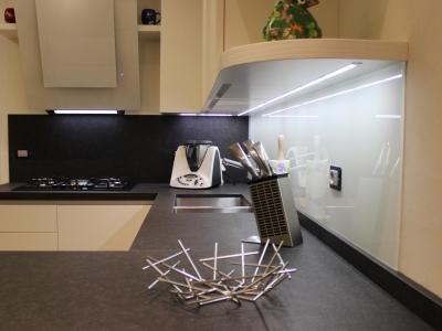 Нашло применение дизайнерской комбинации стеновой панели столешницы и стекла. Зона стеклянной панели подсвечивается светильниками полок