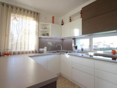 Высокий глянец  фасадов   нижних и верхних ящиков кухни хорошо сочетает с натуральным шпоном дерева