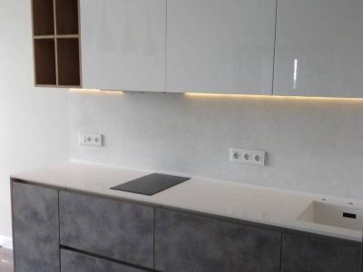 Верхние глянцевые фасады кухни разбавляют серые бетонные тона