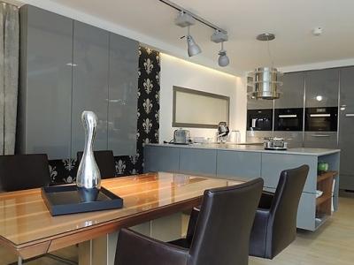 Современная угловая  кухня. Высокие глянцевые фасады мдф графитовых оттенков хорошо сочетаются с глянцевым шпоном американского ореха