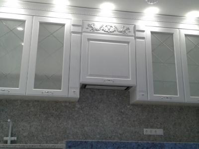 Высокие фасады с витражами с  фрезеровками на матовом стекле и декоративный портал для встраиваемой вытяжки с резными элементами делают кухню торжественной и элегантной