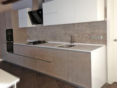 Верхние фасады кухни в матовом белоснежном стекле, вместе с белой столешницей из кварцевого композита, гармонично разбавляют темные тона помещения