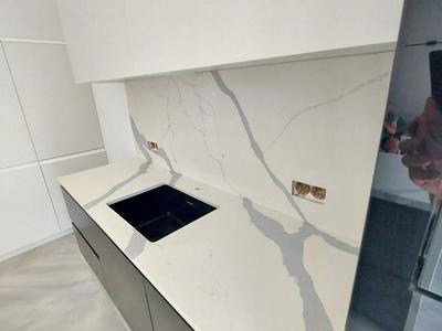 Столешница на кухни вместе со стеновой панелью из кварцевого натурального камня изготовлена с дизайнерским подбором рисунка