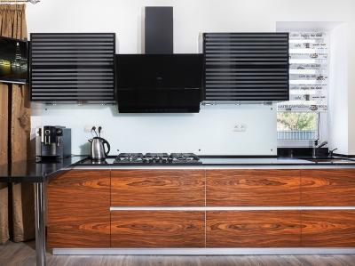 Центральная симметричная часть является визуальным центром всего гарнитура.   Она скрадывает общую сложность дизайна мебели, который  призван компенсировать недостатки помещения.