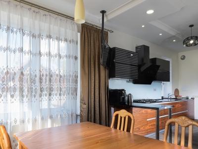 из гостиной комнаты видна основная часть кухни, где эффектная вытяжка является визуальным центром всей композиции.
