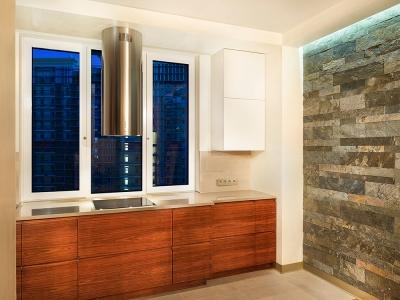 Центральная часть кухни сделана выступающей вперед для большего удобства, плюс такое решение  позволяет  спрятать батарею за шкафами.