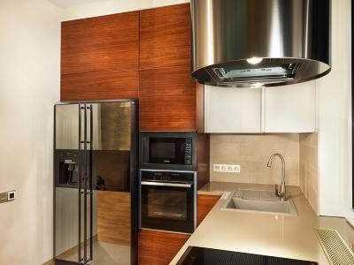 Зеркальная поверхность холодильника зрительно скрадывает ощущение тесного угла, за которым расположена мебель.