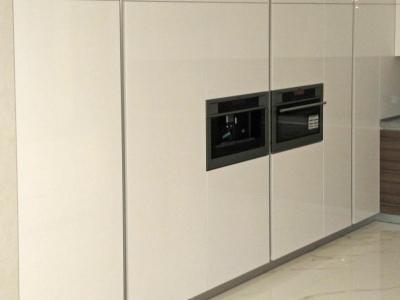 В четырех метровую стену встроены холодильник, морозильник, кофе машина, микроволновая печь, выдвижные высокие карги для хранения мелких припасов