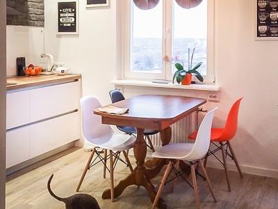Интересное сочетание стола традиционного дизайна из дерева, и стульев из белого и яркого красного пластика.