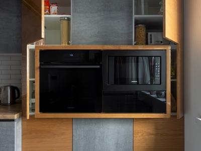 Форма шпонированных фасадов повторяет форму выступающего модуля для встраиваемой техники