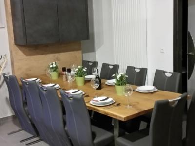 Столешница большого обеденного стола изготовлена из массива и стилистически поддерживает барную стойку