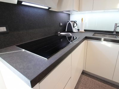 В каменную столешницу кухни встроенная нержавеющая мойка, которая также как и холодильник поддерживают общий стиль