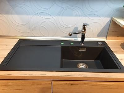 Гранитная мойка, бытовая техника черного цвета подобрана к черному стеклу верхних ящиков кухни