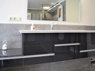 Подвесная тумба в ванной комнате также сочетается с общим стилем мебели на кухне