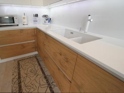 Каменная столешница кухни со стеновой стеклянной панелью поддерживают необходимую роскошь