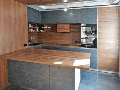 Угловая кухня с полу-островом изготовлена из высококачественных плитных материалов имитирующих камень и дерево