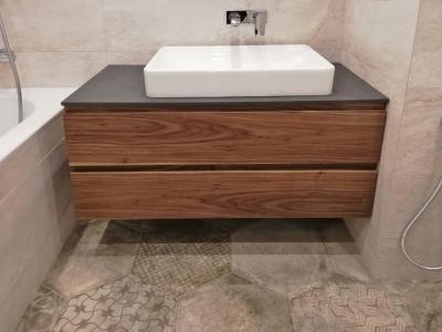 В ванной комнате подвесная тумба имеет керамическую столешницу