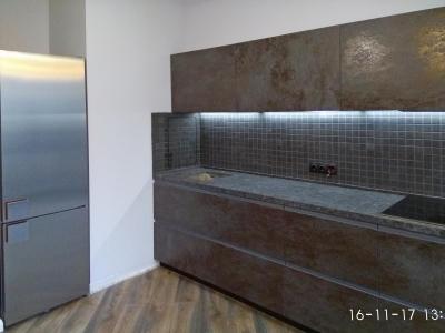 Холодильник под нержавеющую сталь хорошо сочетается с интерьером кухни.